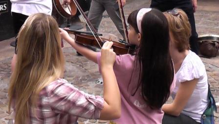 A young future fiddler having a go